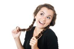 El jugar femenino joven con sus trenzas Imagen de archivo