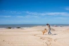 El jugar masculino joven en la playa con un perro del golden retriever Fotografía de archivo