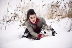 El jugar que camina de la muchacha de la moda de los jóvenes con el perro fornido afuera en parque de la nieve del invierno, divi Fotos de archivo libres de regalías