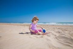 El jugar que se sienta de la niña con la pala azul en playa de la arena Foto de archivo libre de regalías
