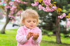 El jugar rubio poco encantador con placer en el jardín con Foto de archivo