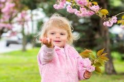 El jugar rubio poco encantador con placer en el jardín Imagenes de archivo