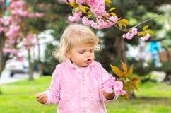 El jugar rubio poco encantador con placer en el jardín Imagen de archivo