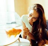 El jugar sonriente de la mujer bonita con el pez de colores en casa, mañana de la luz del sol, concepto de la gente de la forma d Foto de archivo