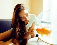 El jugar sonriente de la mujer bonita con el pez de colores en casa, mañana de la luz del sol, concepto de la gente de la forma d Imagen de archivo
