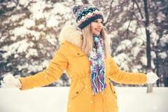 El jugar sonriente feliz del sombrero y de la bufanda de la mujer que lleva joven al aire libre Foto de archivo