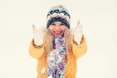 El jugar sonriente feliz del sombrero y de la bufanda de la mujer que lleva joven con la nieve al aire libre Fotos de archivo libres de regalías