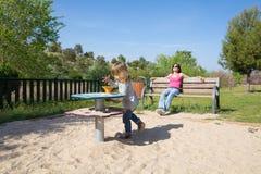 El jugar y madre del niño que descansan en banco Foto de archivo