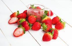 El jugo de la fresa puesto al lado de grupo de fresa roja y de fresa cutted, puso el tablero de la madera imagen de archivo