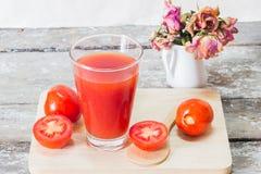El jugo de tomate en hierba con el tomate fresco da fruto Foto de archivo libre de regalías