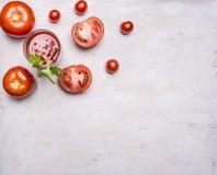 El jugo de tomate fresco en un vidrio con una paja, con la hoja verde, los tomates tajados se separó alrededor de la frontera, ru Fotografía de archivo