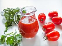 El jugo de tomate se vierte en un jarro de cristal con los tomates en un blanco Fotografía de archivo