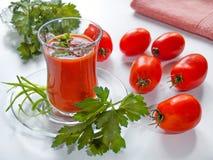 El jugo de tomate se vierte en una taza de cristal en una placa con las hierbas encendido Fotografía de archivo libre de regalías
