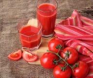 El jugo de tomate vierte en los vidrios Fotos de archivo libres de regalías