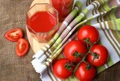 El jugo de tomate vierte en los vidrios Imagen de archivo