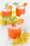 El jugo de zanahoria, el jarro de leche y la mimosa ramifican Foto de archivo