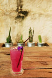 El jugo fresco del guisante de mariposa en la tabla de madera adorna por el cactus en los potes de aluminio y pared áspera del ce Fotografía de archivo