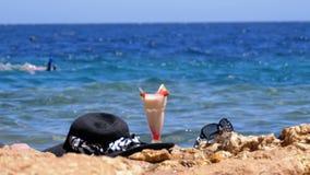 El jugo, el sombrero y los vidrios frescos tropicales en la playa de Egipto defiende en una roca el mar metrajes