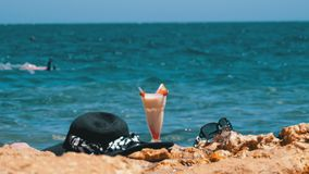 El jugo, el sombrero y los vidrios frescos tropicales en la playa de Egipto defiende en una roca el mar almacen de video