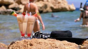 El jugo, el sombrero y los vidrios frescos tropicales en la playa de Egipto defiende en una roca el Mar Rojo almacen de video