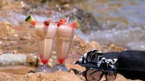 El jugo, el sombrero y los vidrios frescos tropicales en la playa de Egipto defiende en una roca el Mar Rojo almacen de metraje de vídeo