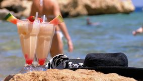 El jugo, el sombrero y los vidrios frescos tropicales en la playa de Egipto defiende en una roca el Mar Rojo metrajes