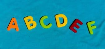 El juguete colorido pone letras a alfabeto en la orden ABCDEF Imágenes de archivo libres de regalías