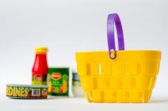 El juguete colorido una cesta de compras está vacío en productos de un fondo Imagen de archivo libre de regalías