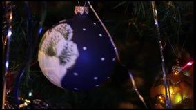 El juguete de la Navidad (bola azul) colgó en un árbol de la Navidad (Año Nuevo) metrajes