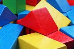 el juguete de madera bloquea el fondo Bloques de madera del juguete del verde rojo, azul, amarillo en el fondo blanco Modelo de l Fotografía de archivo