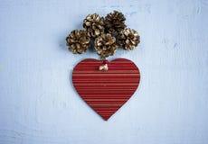 El juguete de madera del corazón adornó endecha plana del pinecone en la parte posterior de madera del azul Imágenes de archivo libres de regalías