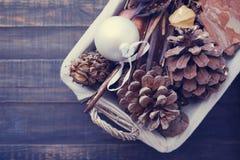El juguete del Año Nuevo, cedro de los conos y paisaje natural por Año Nuevo en una cesta Imagenes de archivo
