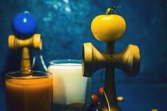 El juguete japonés tradicional del ` de Kendama del ` y la comida sana por adolescencias embroma salud de niños del concepto de l Fotografía de archivo libre de regalías