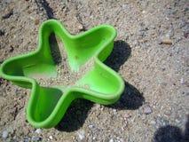 El juguete plástico verde de la arena formó como una estrella de mar que mentía en la arena imagen de archivo