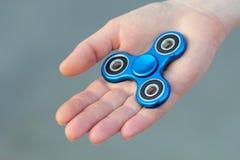 El juguete popular del hilandero de la persona agitada del metal azul en la palma de su mano, la toma Fotografía de archivo