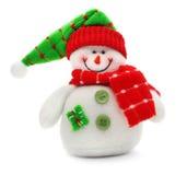 El juguete sonriente del muñeco de nieve se vistió en bufanda y casquillo Fotografía de archivo libre de regalías