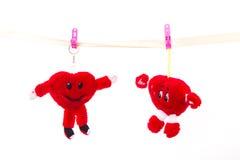 El juguete suave ató con correa las pinzas que colgaban el corazón el día del ` s de la tarjeta del día de San Valentín Imagen de archivo