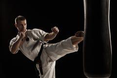 El karate redondo golpea adentro un saco de arena con el pie Foto de archivo