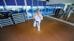 El karate rubio deportivo del entrenamiento engaña en el gimnasio almacen de metraje de vídeo