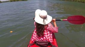 El kayaking de batimiento de la mujer en la cámara hermosa pov de la acción de la laguna de la muchacha que se sienta en el barco almacen de metraje de vídeo
