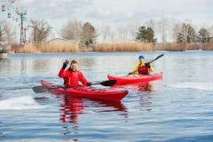 El kayaking de dos mangos en el kajak rojo en el río 01 Fotos de archivo