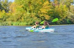 El kayaking de la familia, madre y niño batiéndose en kajak en viaje de la canoa del río, fin de semana activo del verano y vacac Fotografía de archivo libre de regalías