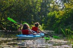 El kayaking de la familia, madre y niño batiéndose en kajak en viaje de la canoa del río, fin de semana y vacaciones activas del  Imagen de archivo libre de regalías
