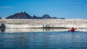 El Kayaking delante de un glaciar Imagen de archivo libre de regalías