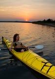 El Kayaking en la puesta del sol Imágenes de archivo libres de regalías