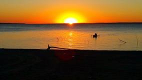 El Kayaking en la puesta del sol foto de archivo