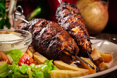 El kebab asado a la parrilla sirvió con los microprocesadores y la ensalada fritos Foto de archivo