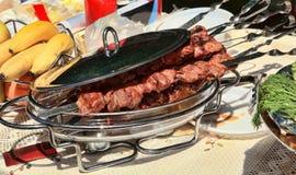 El kebab caucásico en los pinchos en un plato con una tapa para a Imagen de archivo libre de regalías
