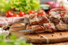 El kebab jugoso y apetitoso del cerdo cocinó en el fuego abierto y las verduras frescas Aún-vida en un fondo de madera Fotos de archivo