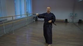 El kendo principal conduce el entrenamiento con la espada del catana, realiza kata en el pasillo de deportes con los espejos metrajes
